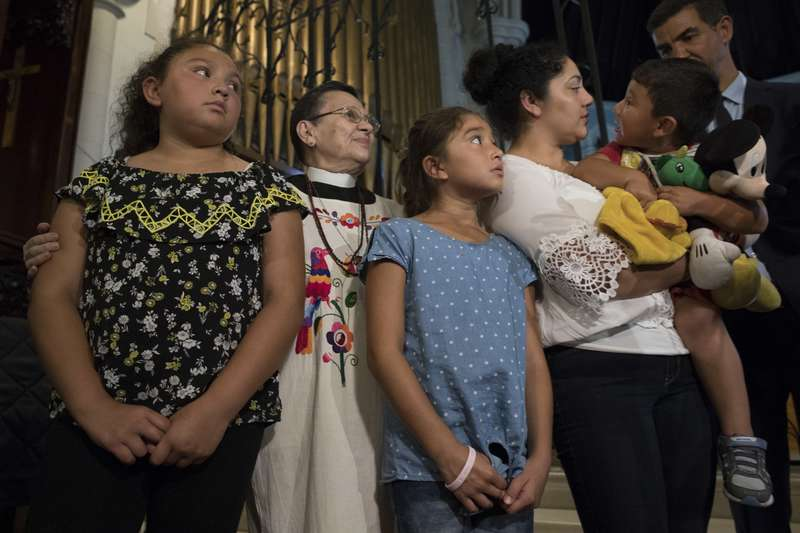 The Reverend Maria Santiviago, second from left, assistant pastor at the Holyrood Church, stands with Amanda Morales, second from right, and her children Dulce Carvajal, left, Daniela Carvajal, center, and David Carvajal during a news conference at the church in the Washington Heights neighborhood of Manhattan, Thursday, Aug. 17, 2017. Morales who is originally from Guatemala and has lived without authorization in the U.S. since 2004 has taken sanctuary at the church. (AP Photo/Mary Altaffer)